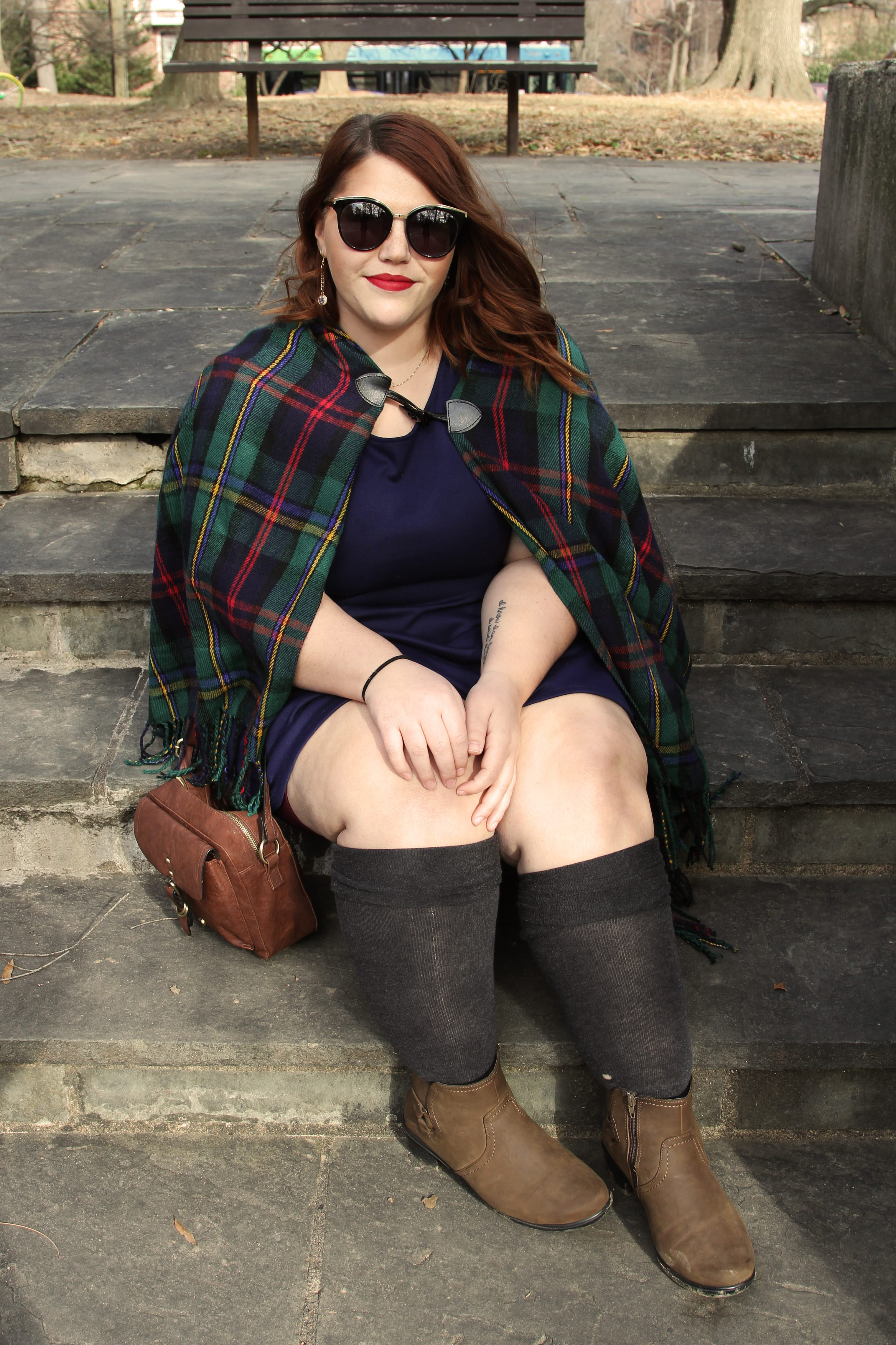 Femme woman sitting on stone stairs wearing a blue dress, grey knee socks, a plaid cape, red lipstick, big sunglasses, and smiling.