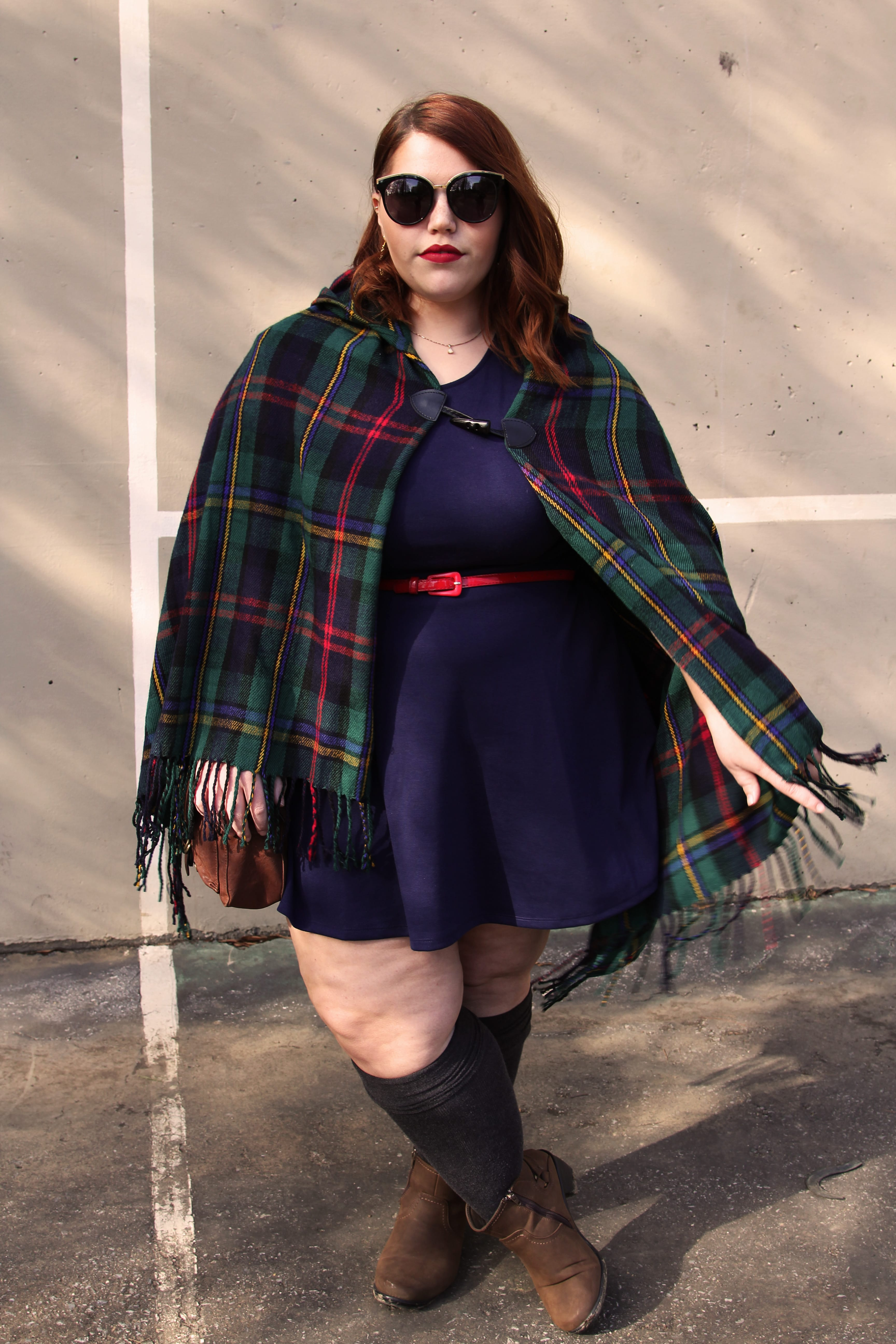 Plus size femme-presenting woman wearing a short blue dress with a thin red belt. She's also wearing a plaid cape with green, red, yellow, and blue colors. She's wearing red lipstick, big sunglasses, gray knee socks, and her hair is red and in loose curls.