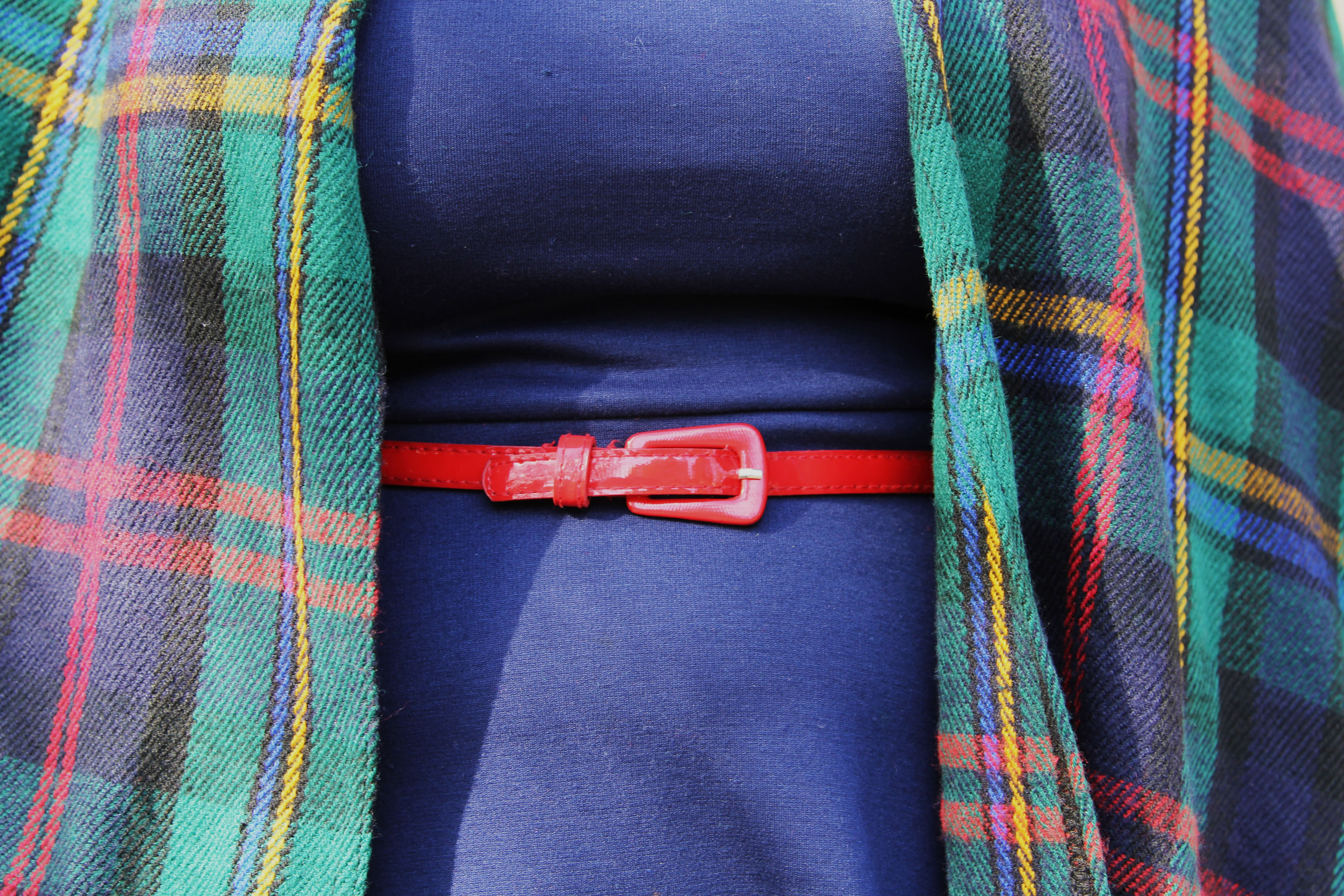 Close up of a fat woman's midsection. The blue dress, red belt, and part of the plaid cape are visible.