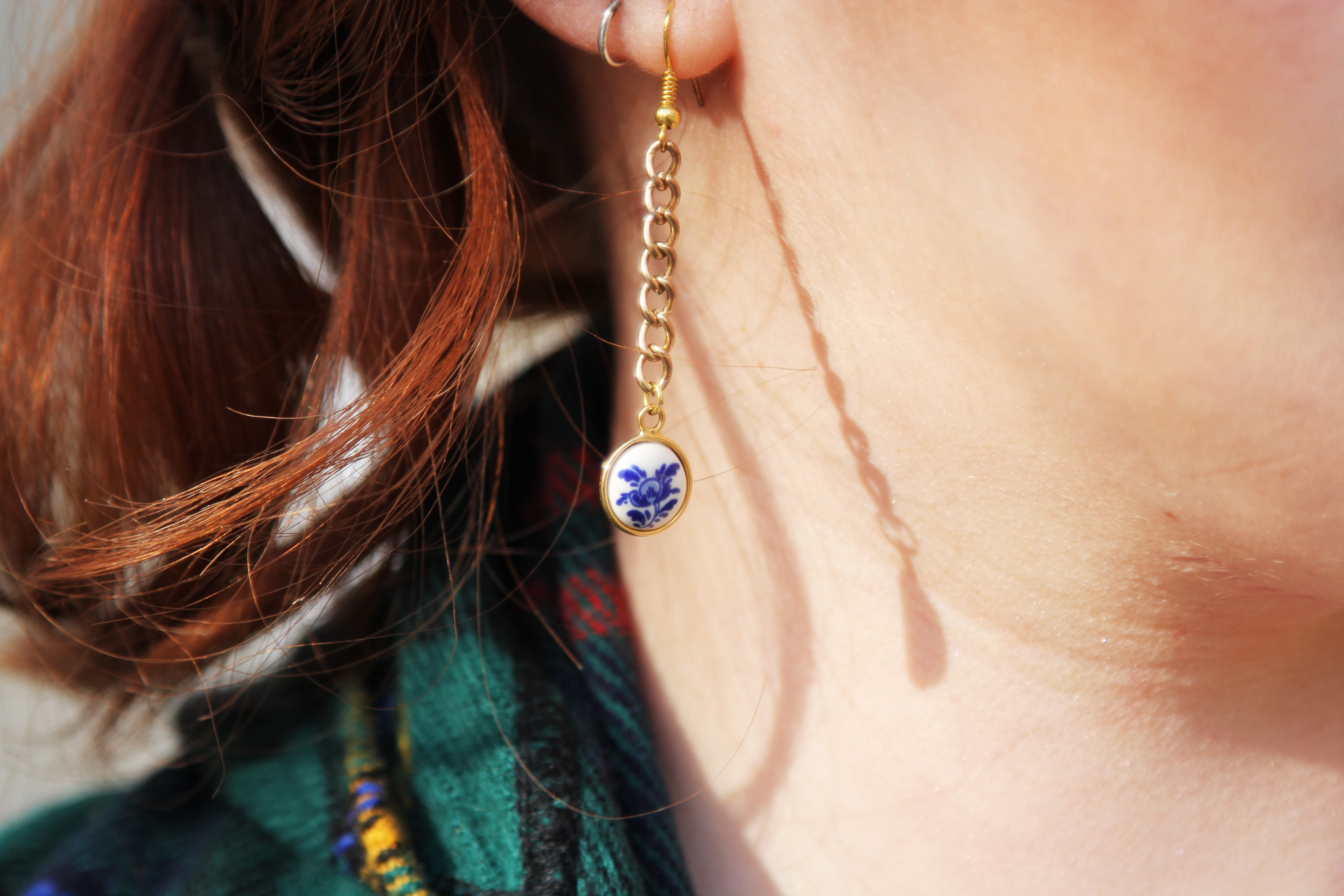 Close up shot of a fat person's neck and lower ear. Center of photo is an dangling earring with a gold chain.