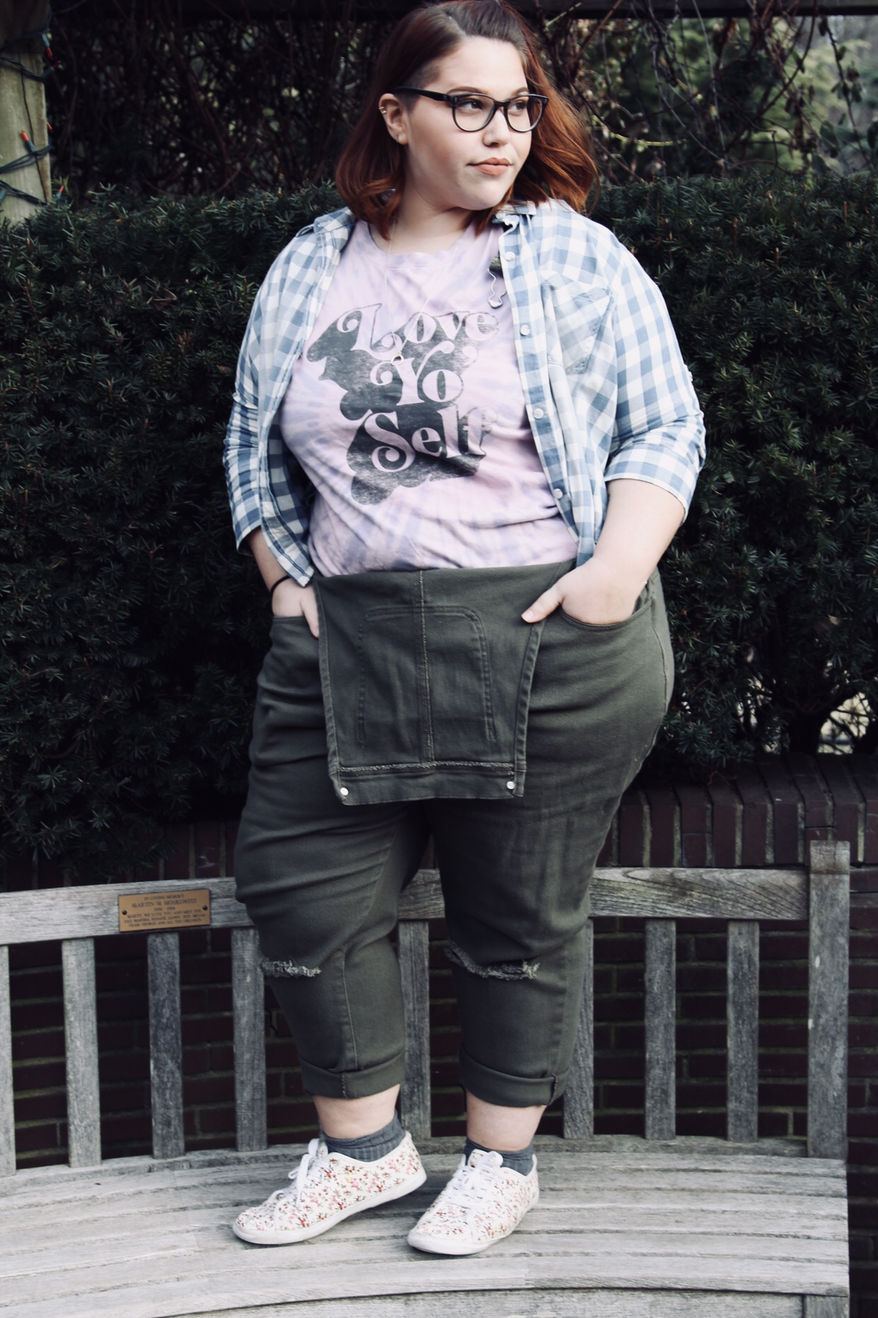 """Femme-presenting plus size women with red shoulder-length hair and black glasses stands on a bench with her hands in her pockets. She is wearing a light purple t-shirt with the phrase """"Love Yo Self"""" on it, a blue and white gingham button up worn open, olive green overalls that aren't suspended, and floral sneakers."""